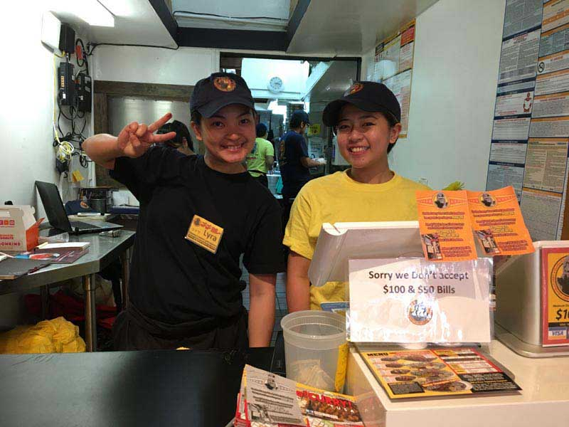 Two happy employees smile behind the counter at Go! Go! Curry!