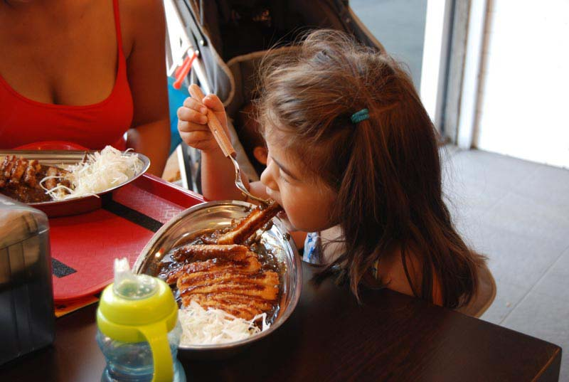 An enthusiastic child noms on a piece of fried katsu cutlet.