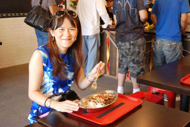 A happy customer smiles with content happiness at Go! Go! Curry! after eating her curry dish.