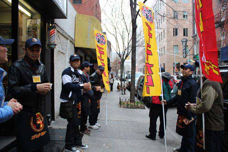 Employees stand outside advertising the Best curry in town with Japanese flags.