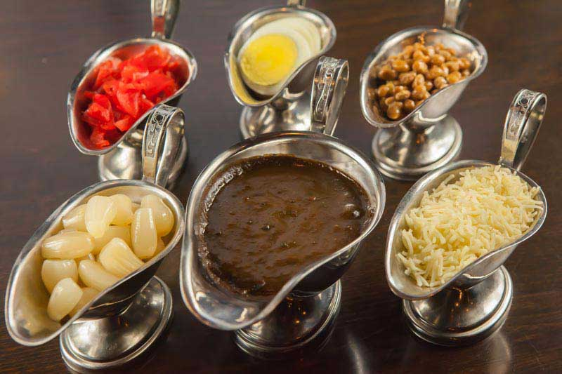 Top notch ingredients. Side dishes for the Japanese curry displayed in metal pourers, including rakkyo (pickled shallots), fukujinzuke (pickled radish), natto, boiled egg, and shredded cheese.including
