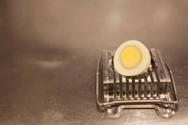 Premium boiled sliced egg on a counter with a slicer